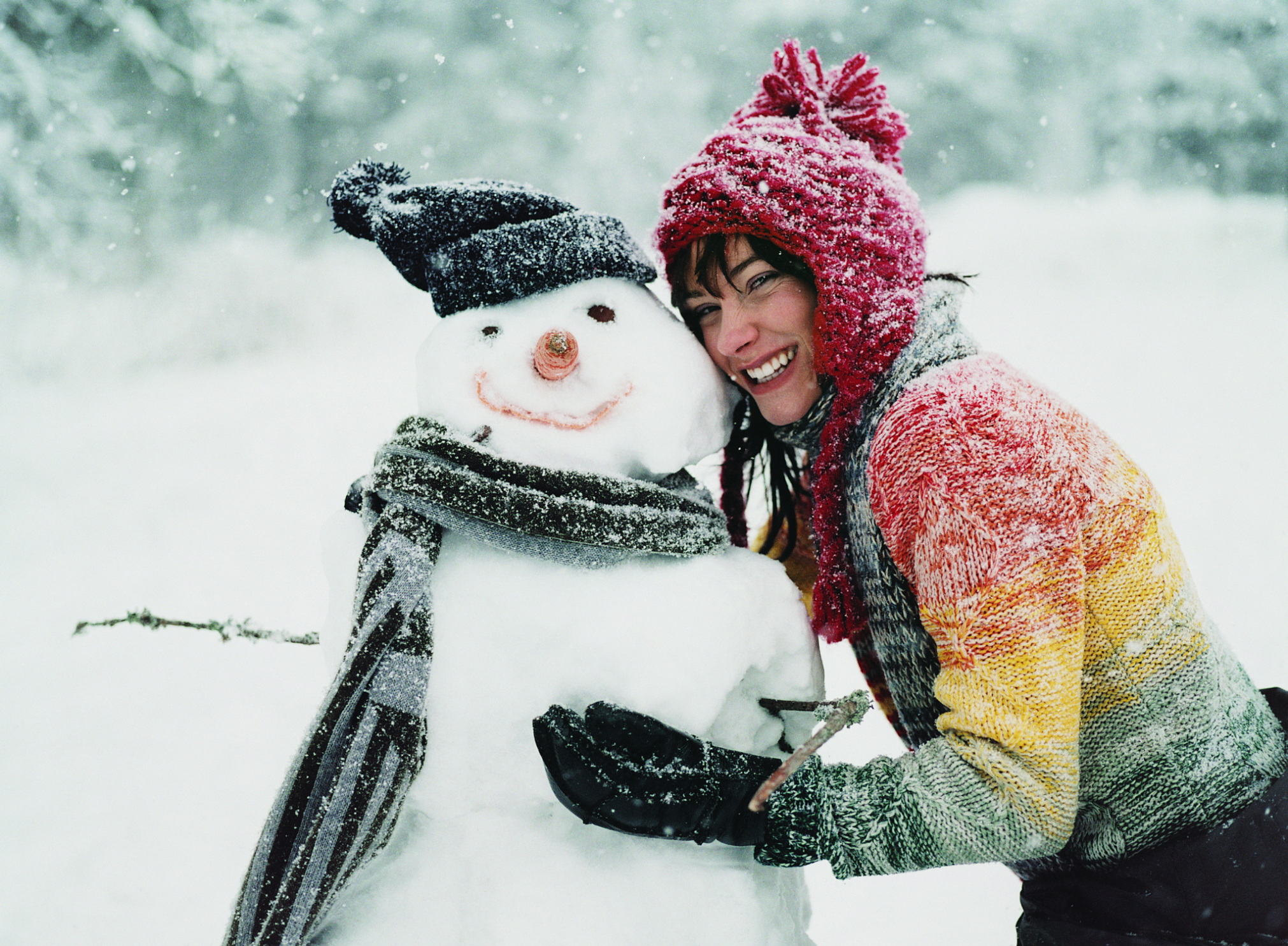 Portrait of a Young Woman in the Snow Next to a Snowman
